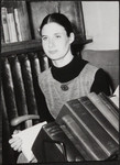 [Photograph of Jay Macpherson sitting holding a book with books in front of her]