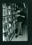 Student standing in stacks reading a book