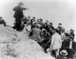 A. P. Coleman addressing a group of geologists (?) by a shore. :: A. P. Coleman sadressant à un groupe de géologue (?) par un rivage.