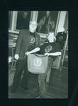 Ann Black holding book sale bag beside volunteer in Victoria College Building
