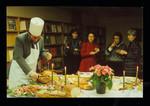 Robert Brandeis carving Christmas turkey at Pratt Library as librarians look on