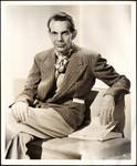 Raymond Massey sitting on settee with script