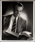 Raymond Massey holding book
