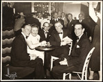 Raymond Massey with Walter Huston and others at table in bar