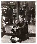 """Raymond Massey sitting on curbside holding tattered newspaper in the rain in """"The Fountainhead"""""""