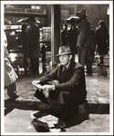 "Raymond Massey sitting on curbside holding tattered newspaper in the rain in ""The Fountainhead"""