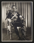 """Raymond Massey as character in """"The Scarlet Pimpernel"""" sitting on throne"""